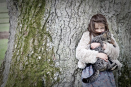 Girl holding a cat leaning against a tree