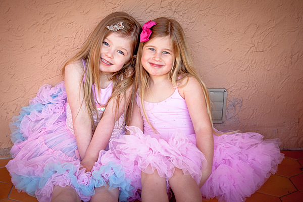 Two small girls in pink dresses sitting on a bench
